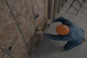 picture of a carpenter installing commercial sound and thermal insulation